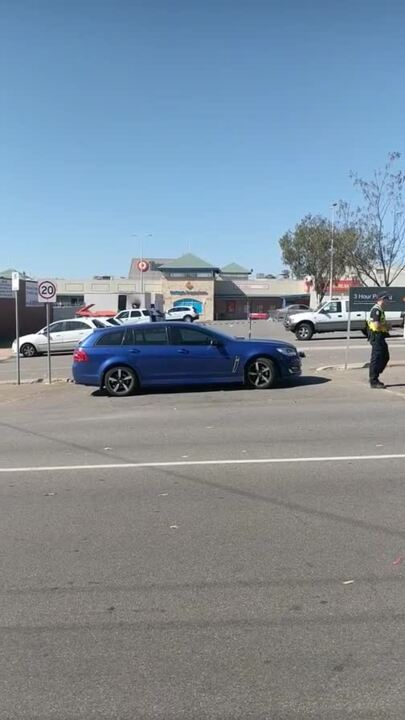 An unmarked police car and officer block an entrance to Northgate Shopping Centre.