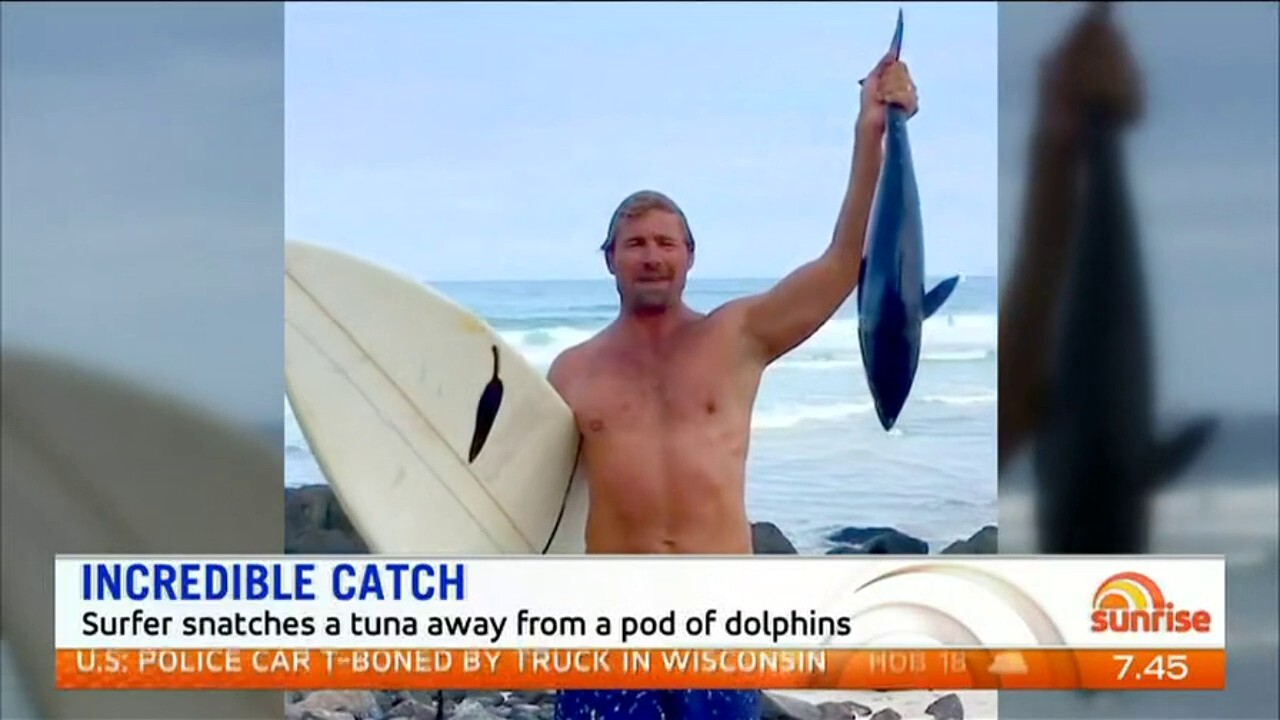 Surfer Nick Smith stunned onlookers when he snatched a tuna from a pod of dolphins
