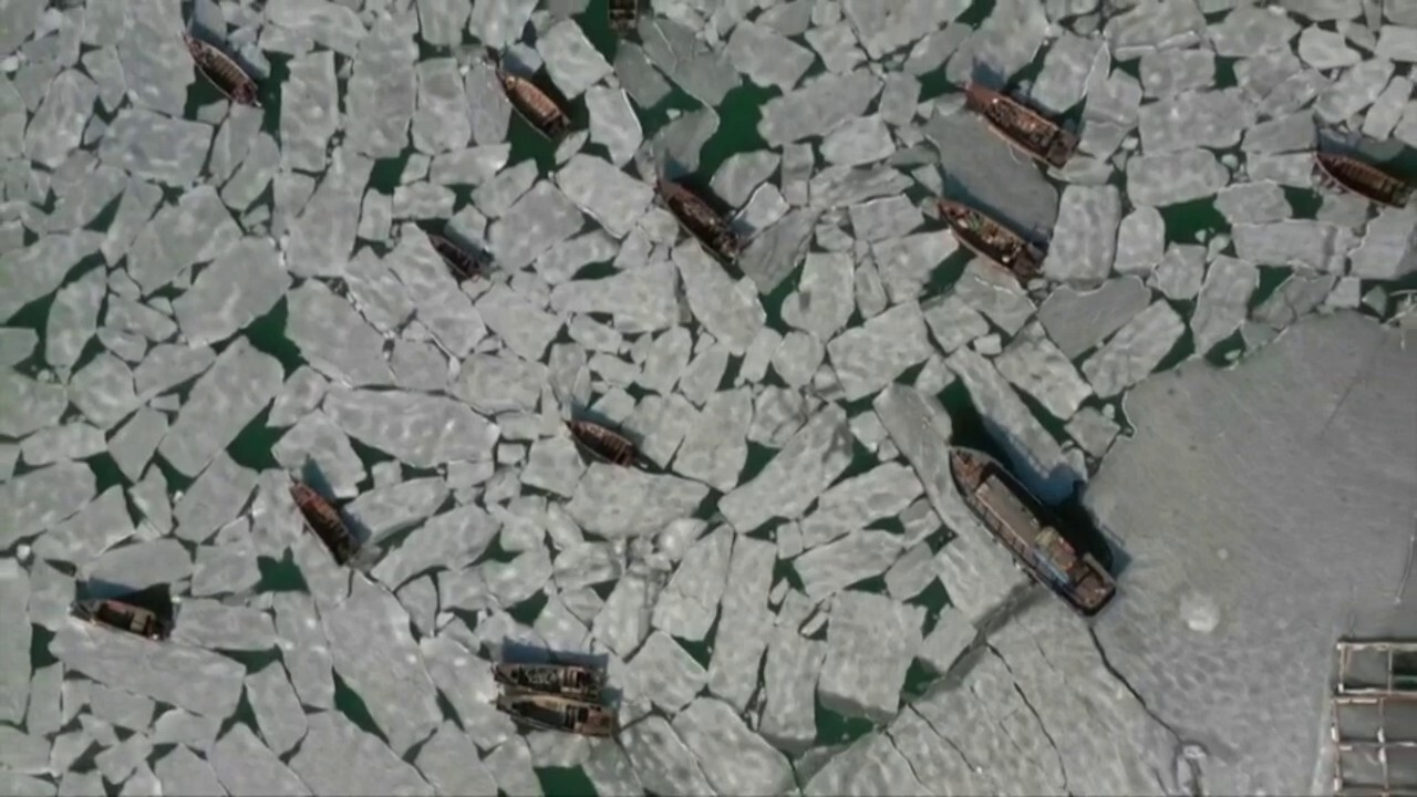 Hundreds of fishing boats have been stranded at a frozen port in China